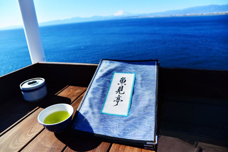 Close-up of coffee cup on table by sea against sky