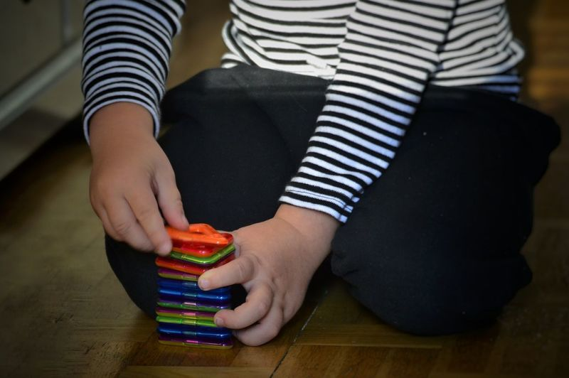 Midsection of boy playing with toys on floor