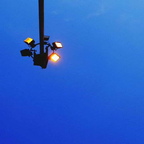 Low angle view of illuminated lighting against clear blue sky