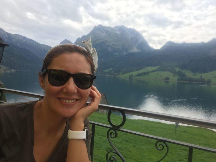 Portrait of woman wearing sunglasses against lake
