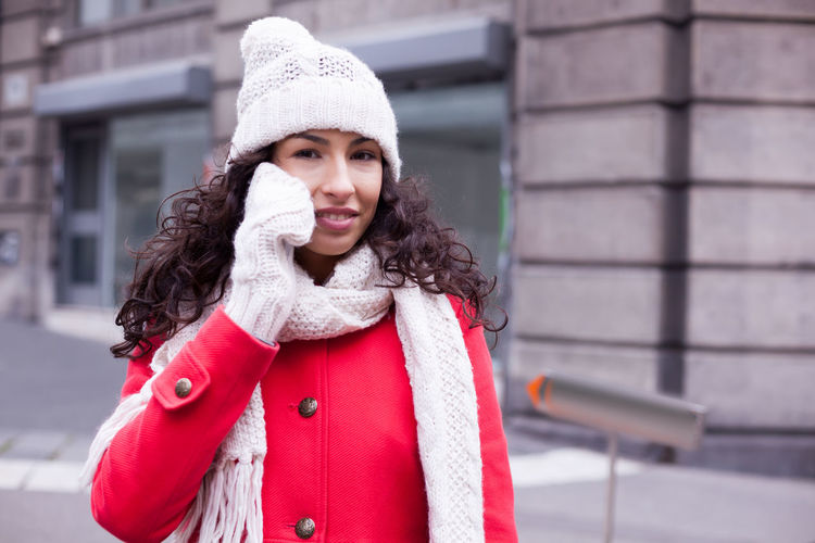 Portrait of young woman talking on smart phone while standing on city street