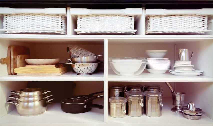 Containers and ceramics arranged in shelves at kitchen