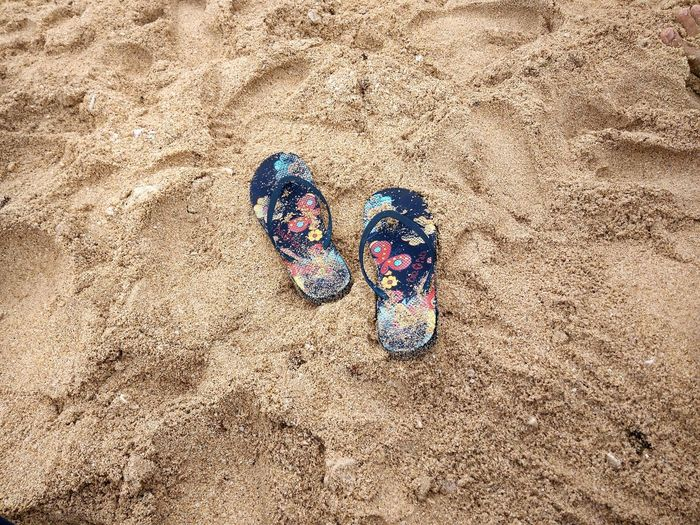 Low section of shoes on sand