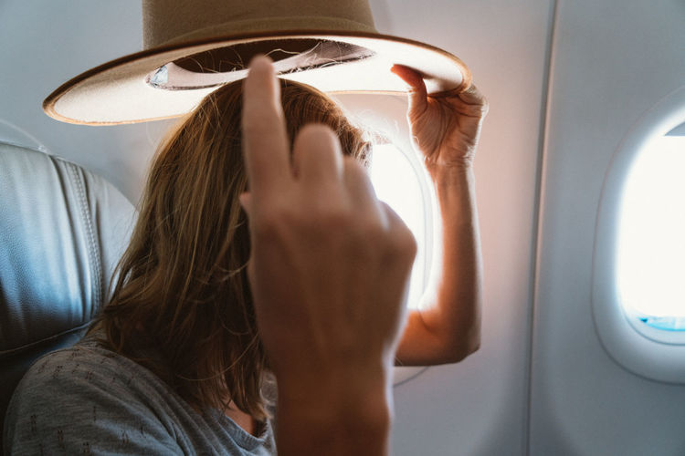 Woman putting on hat in the airplane