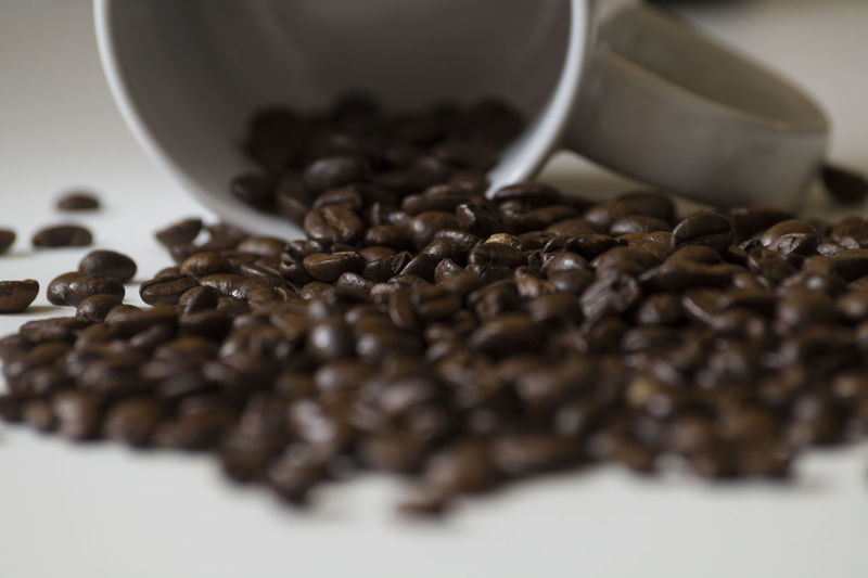 Close-up of roasted coffee beans and cup on table