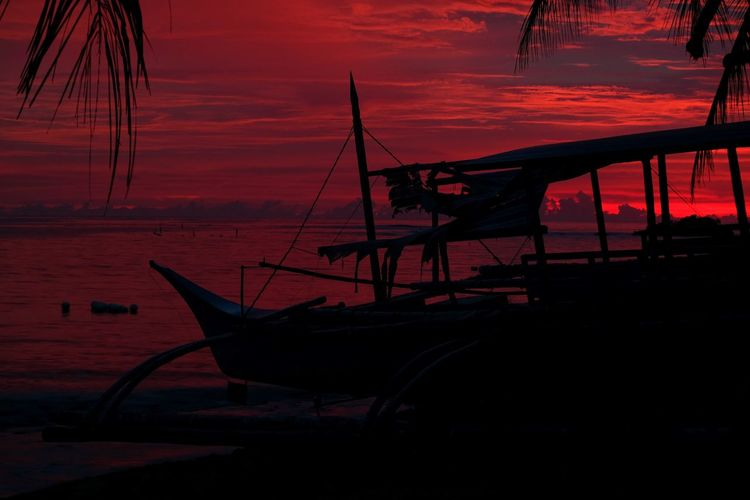 Silhouette of fishing boat in sea during sunset