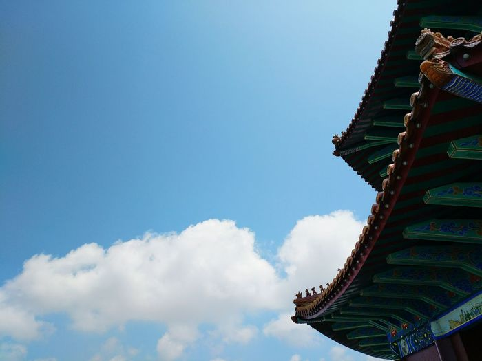 Low angle view of building roof against blue sky