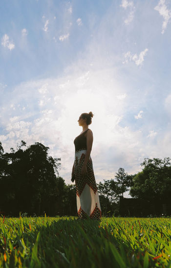 Woman with flowers on grass against sky