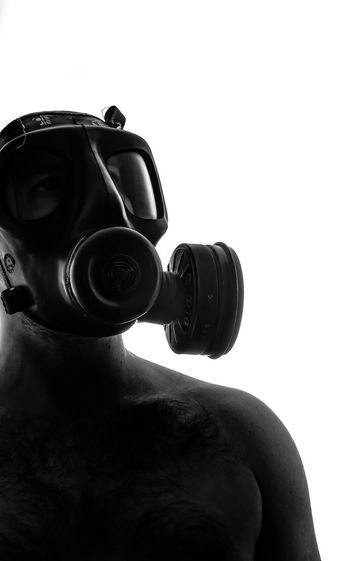 Close-up of shirtless man wearing gas mask against clear sky