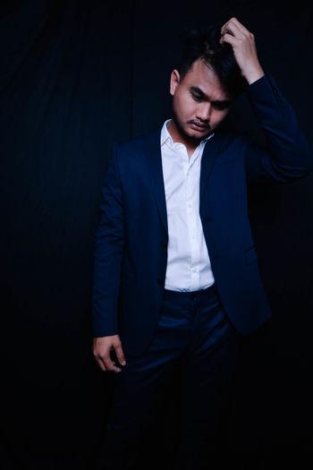 Businessman standing against black background