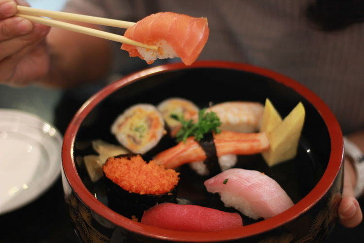 Midsection of person holding sushi in container