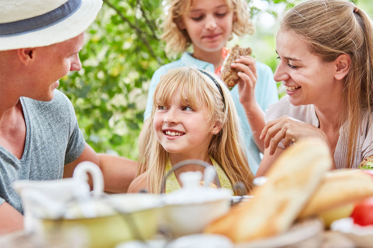 Smiling family having breakfast while sitting at table outdoors