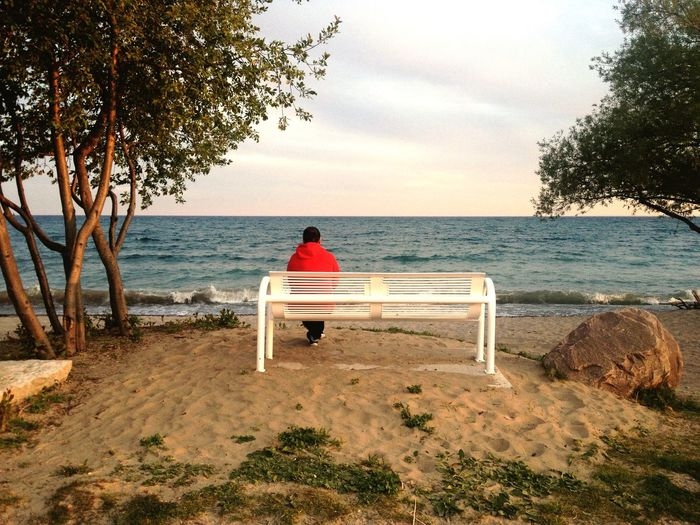 Rear View Of Man Sitting At Bench Against Sky