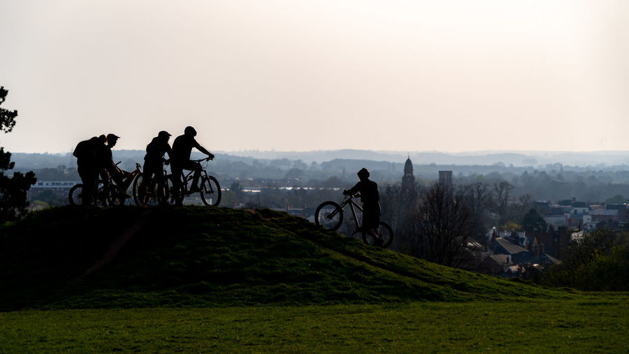 Teens meeting at bicycle riding track set against sky