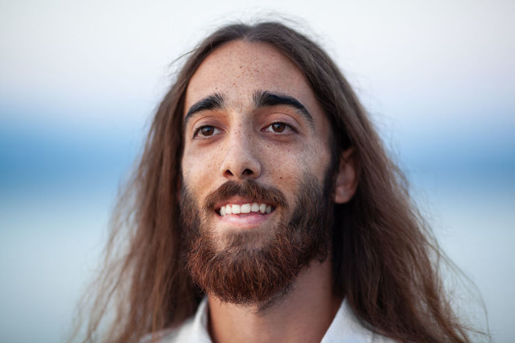 Smiling bearded young man with long brown hair looking away