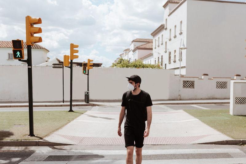 Full length of man standing on road against sky in city