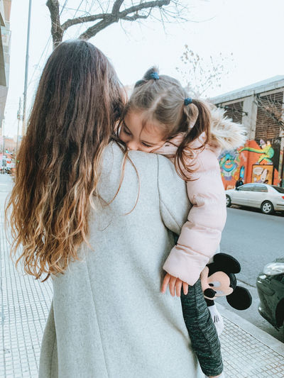 Mother and girl with arms raised outdoors