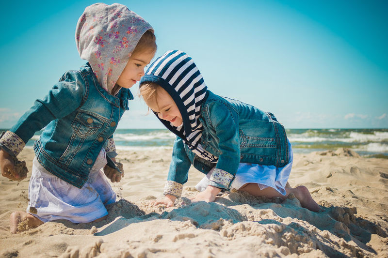 Beach Sea Sand Summer Kid Childhood Girl Twig Sister Sisters Land Child Males  Two People Sky Nature Leisure Activity Men Boys Togetherness Real People Casual Clothing Lifestyles People Water Innocence Outdoors Positive Emotion