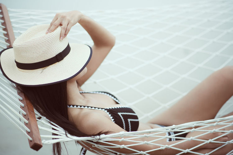 Hat One Person Clothing Leisure Activity Adult Women Young Adult Sitting Real People Relaxation Sun Hat Young Women Lifestyles Day Focus On Foreground Summer Fashion White Color Outdoors Beautiful Woman Swimming Pool Hairstyle