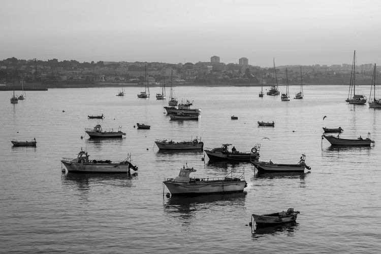 Boats moored on river against sky in city