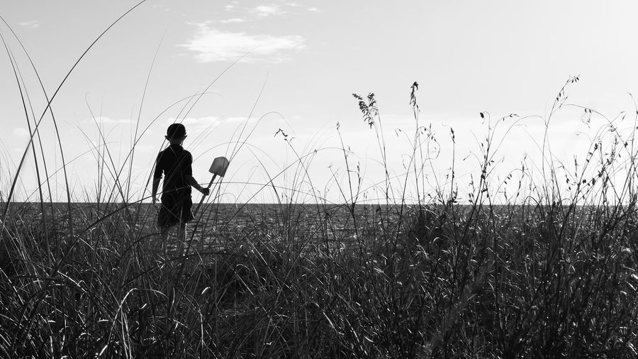 Grass against silhouette boy with shovel standing at beach