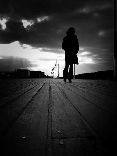 Surface level of silhouette man walking on wooden floor