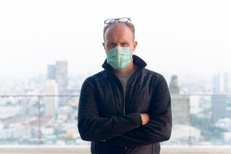Portrait of mature man standing against cityscape