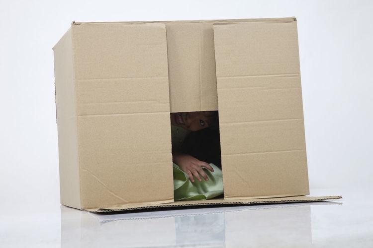 Girl In Cardboard Box Against White Background