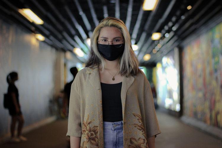 Portrait of woman standing in corridor of building