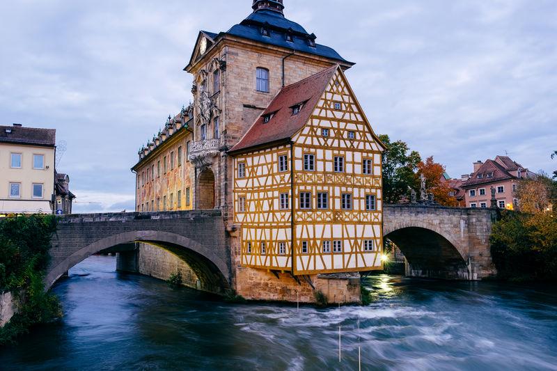 Arch Bridge Over River Against Buildings