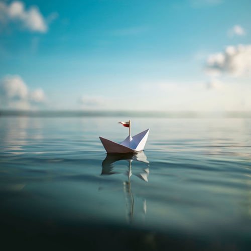 Close-up of paper boat floating on lake against sky
