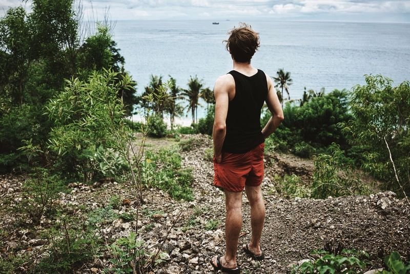 View Sea Man Standing Watching Nature Traveling Holiday Adventure Red Shorts Tanktop INDONESIA Bali Padangbai Bias Tegul White Sand Beach