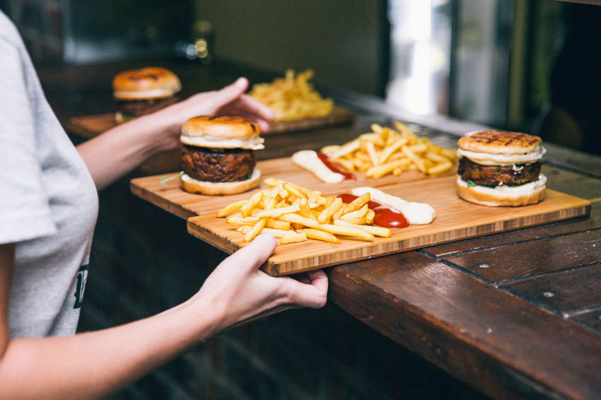 Bar Food Burger Fast Food Focus On Foreground Food Food And Drink French Fries Freshness Fried Hamburger Hamburgers Human Hand Indoors  Potato Prepared Potato Ready-to-eat Real People Relish Sandwich Snack Table Take Out Food Tray Unhealthy Eating