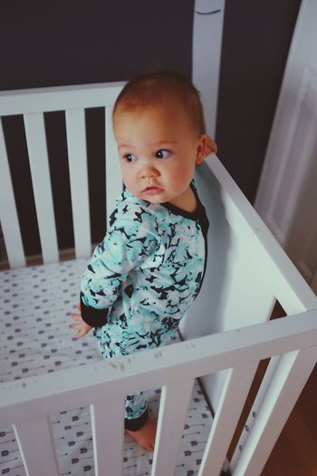 High angle view of baby looking away while standing in crib at home