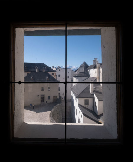 The Salzburg castles out of the window. Window Architecture Glass - Material Transparent Day Building Built Structure Nature Indoors  Sunlight No People Sky Reflection House City Mountain Residential District Window Frame