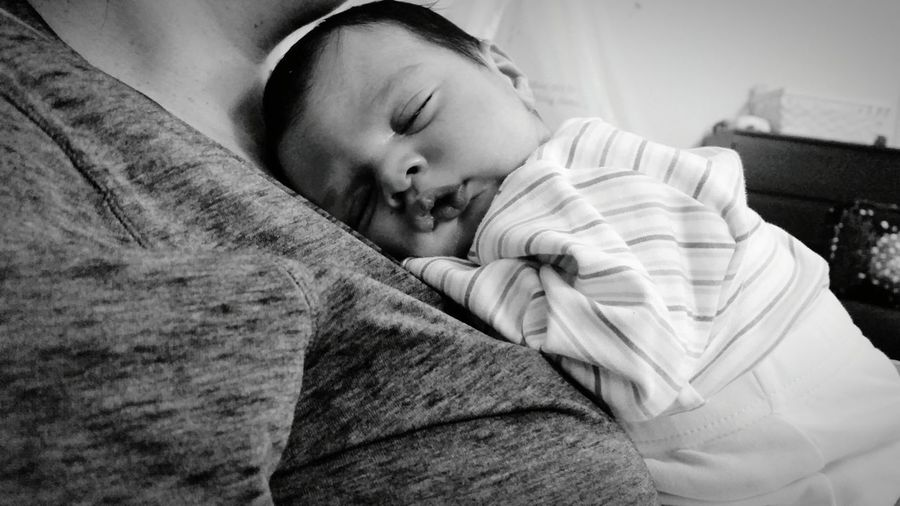 Midsection of woman with sleeping baby boy at home
