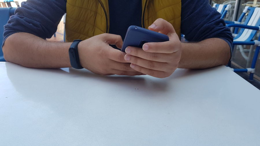 Midsection of man using mobile phone on table