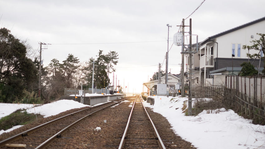 Architecture Building Exterior Built Structure Cable Cold Temperature Diminishing Perspective Direction Electricity  Mode Of Transportation Nature No People Outdoors Plant Rail Transportation Railroad Track Sky Snow The Way Forward Track Train Transportation Tree Winter
