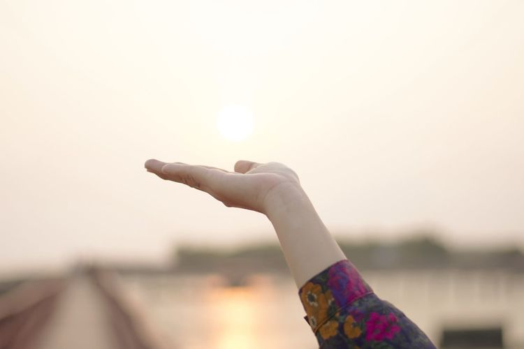 Cropped hand gesturing against sky during sunset