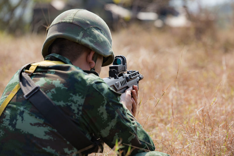 Close-Up Of Army Soldier Shooting With Rifle