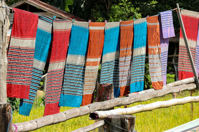 Thai traditional pattern cloth hanging above harvest rice farm Multi Colored Hanging Drying Textile No People Day Striped Choice Variation Clothesline Clothing Nature Laundry Outdoors Plant Focus On Foreground Side By Side Pattern Sunlight Flag Cloth Thailand Northern Thailand Light Sunny