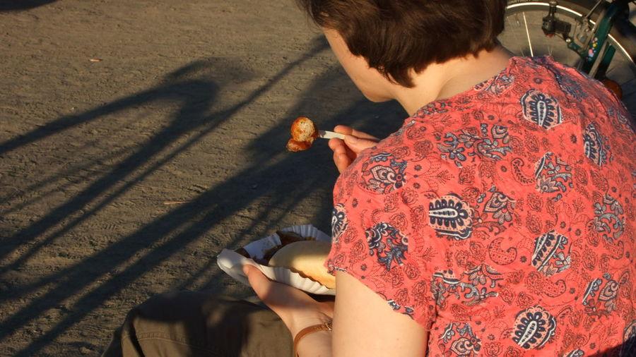 Woman Having Food While Sitting On Sidewalk