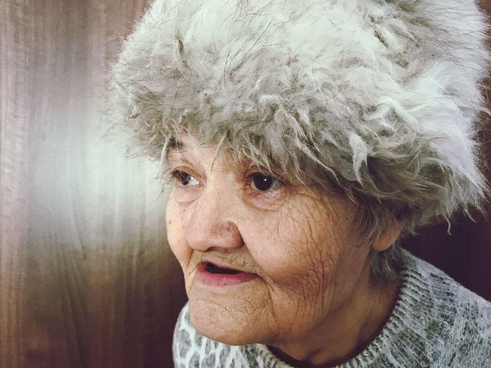 Close-Up Of Senior Woman With Fur Hat Looking Away