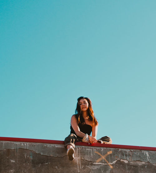 Low angle portrait of smiling young woman sitting on wall against clear blue sky