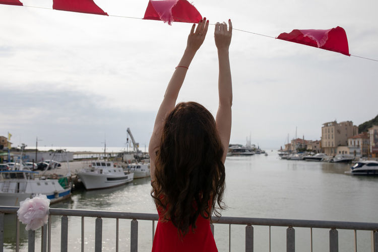 Rear view of woman holding bunting flag hanging at harbor