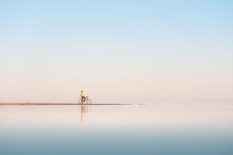 Cyclist on the shore of the calm sea. distant plan