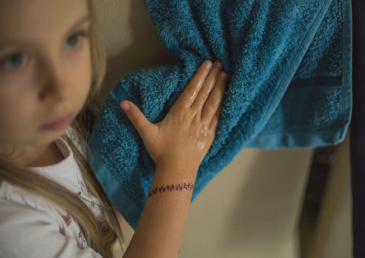Close-up of girl drying hands by using towel at home