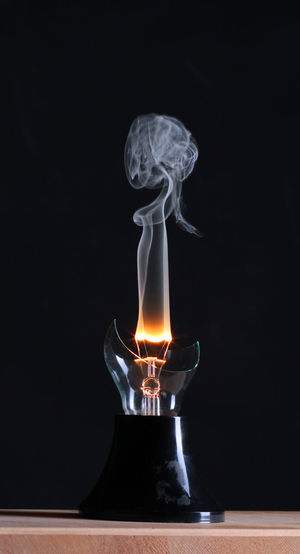 Close-up of smoke emitting from broken illuminated light bulb against black background