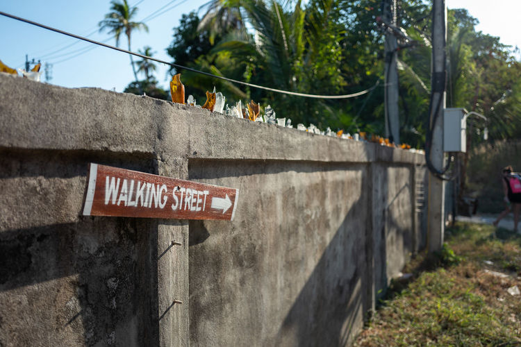 Koh Lipe Text Communication Sign Western Script Day Nature Plant Architecture No People Information Warning Sign Fence Built Structure Outdoors Information Sign Focus On Foreground Boundary Guidance Barrier Capital Letter