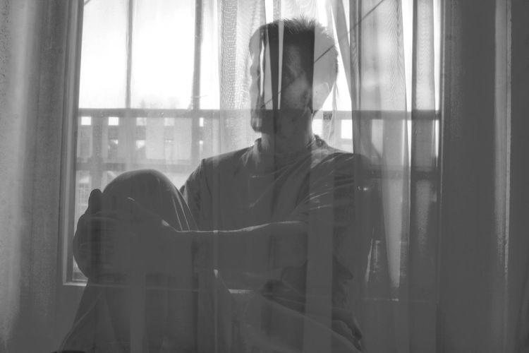 Man sitting by window seen through curtain